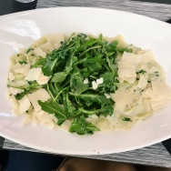 Ravioli in cream sauce with shaved parmesan and arugula